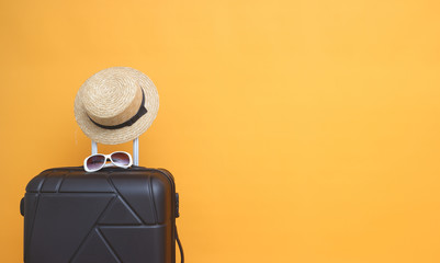 Black suitcase with sun glasses, hat  on pastel yellow   background. travel concept. minimal style