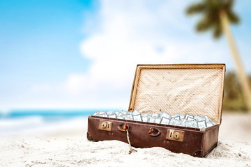Suitcase on beach and ice cubes