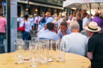 Outdoor sunny selected focus at empty  glasses of beer stand on wooden table on walking street, and blur background of people stand, sit, hang out and drink beer in old town Düsseldorf, Germany.