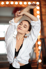 Young brunette woman posing near big mirror. Perfect makeup and stylish ponytail, masculine style, slim figure