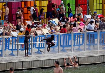 People enjoy the three swimming areas open up along the Bassin de la Villette, as part of the Paris Plages event in Paris