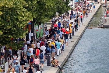 People walk along the Bassin de la Villette, as part of the Paris Plages event in Paris