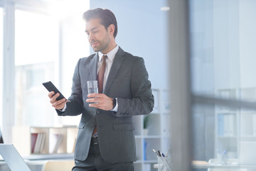 Young confident agent with glass of water scrolling in smartphone