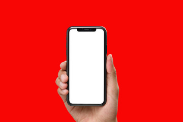 Hand holding the black smartphone with blank screen and modern frame less design on red colour background