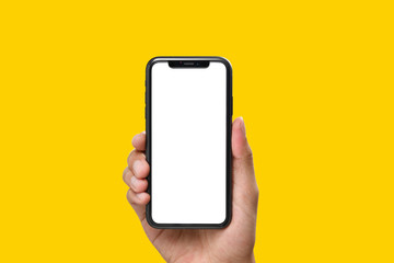 Hand holding the black smartphone with blank screen and modern frame less design on yellow colour background Wall mural