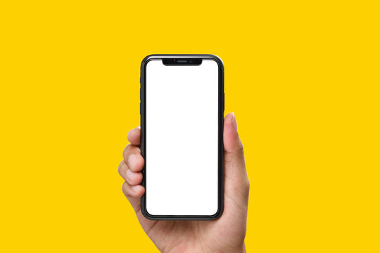 Hand holding the black smartphone with blank screen and modern frame less design on yellow colour background