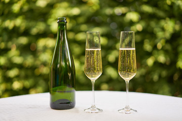 Two wine glasses flute type with sparkling wine or champagne and traditional design champagne bottle on the table with white tablecloth in the romantic garden restaurant ready to celebrate or cheers.