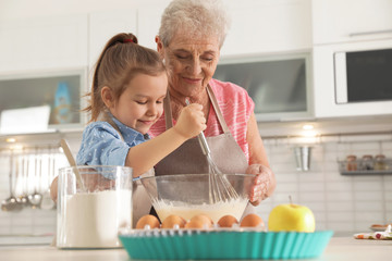 Cute girl and her grandmother cooking in kitchen