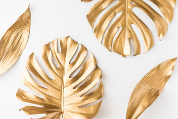 Flat lay of gold tropical palm leaves Monstera on white background. Top view of minimal concept.