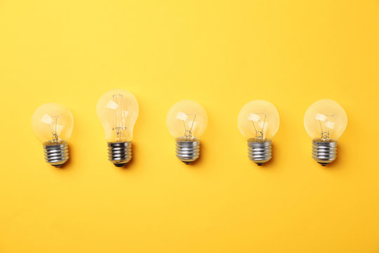 Vintage and modern incandescent lamp bulbs on yellow background, flat lay