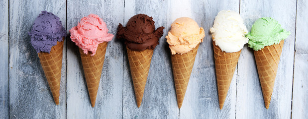 ice cream scoops of different colors and flavours with berries, nuts and fruits decoration on white background