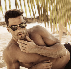 Keuken foto achterwand Artist KB Portrait of a handsome, muscular man relaxing on a beach