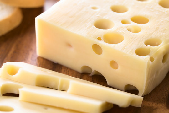 Piece of Emmental, Emmentaler or Emmenthal cheese on wooden plate (Selective Focus, Focus one third into the cheese piece)