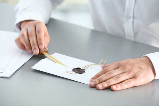 Male notary removing seal from document at table, closeup