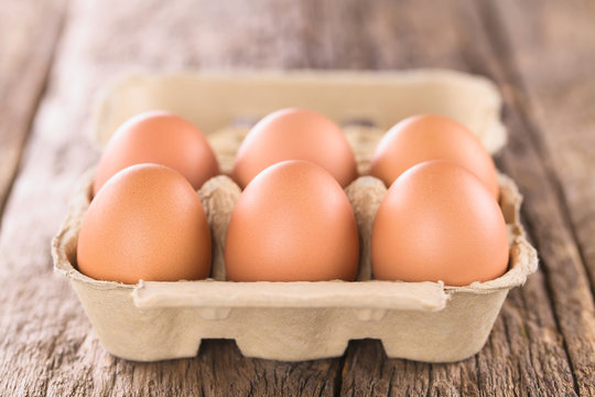 Raw brown eggs in egg box or carton (Very Shallow Depth of Field, Focus on the front of the first eggs)