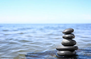 Stack of stones in sea water, space for text. Zen concept