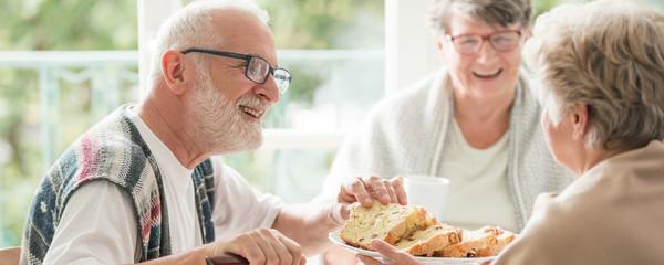 Happy seniors sharing cake during coffee meeting at nursing home