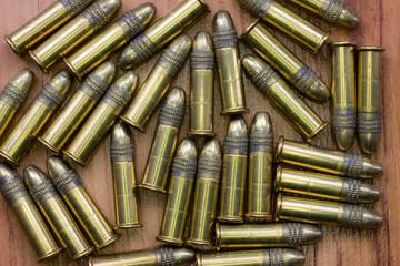 Scattered 22 caliber bullets on wooden background