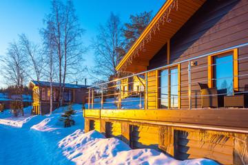 Cottage with veranda on sunny winter day. Winter villa near the forest. Karelian holiday resort. New year rest in Karelia. Cottage for rest weekend. Rent a cottage in Karelia for Christmas holidays.