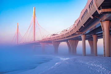 Modern highway. Highway on stilts. Route on a foggy winter morning. Expressway. City road junction. The architecture of the bridges. Road viaduct.