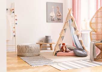 Wicker peacock chair next to tent with pillows and pouf in scandinavian designed girl's playroom, real photo
