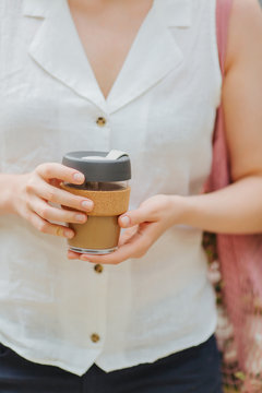 Female hands hold reusable coffee mug.  Sustainable lifestyle. Eco friendly concept.