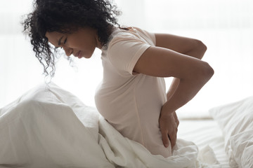 Sad young african woman touching back feeling backache in bed