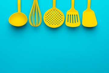 Bright yellow plastic kitchen utensils - cooking concept. Flat lay image of ladle, whisk, skimmer spoon and spatulas with copy space. Upside position of kitchenware on turquoise blue background