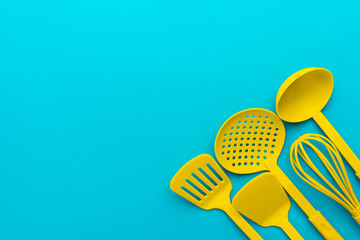 Top view photo of vivid plastic kitchen utensils. Flat lay image of yellow ladle, whisk, skimmer spoon and spatulas over turquoise blue background with copy space. Handy kitchenware on blue table.