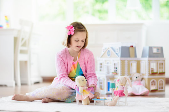 Little girl playing with doll house. Kid with toys