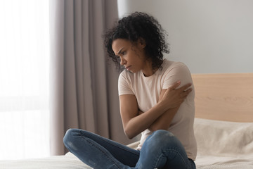 Upset depressed african woman feel sad sit alone on bed Wall mural