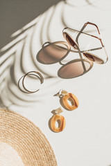 Fashion composition with women's accessories on white background. Earrings, sunglasses, bracelet, straw hat on white background. Flat lay, top view lifestyle blog concept.