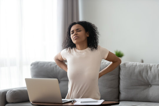 African woman feeling backpain tired of computer sit on sofa