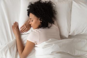 Fototapeta Healthy serene african girl sleeping in comfortable bed, top view obraz