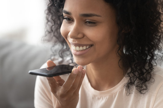 Smiling african woman activate virtual digital voice assistant on smartphone