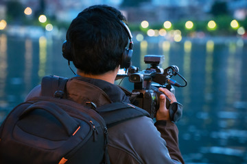 Operator with professional camera shooting night city.