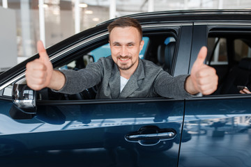 Man in new car shows thumbs up, showroom
