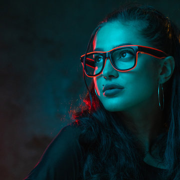 Sensual woman in neon glasses portrait. Beautiful younf female model wearing pink neon glasses isolated over concete wall background
