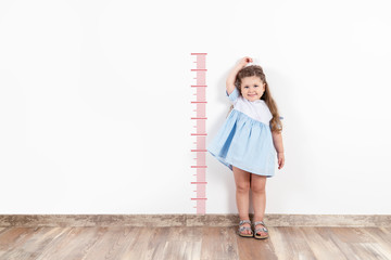 Little blond girl measuring height on white wall.