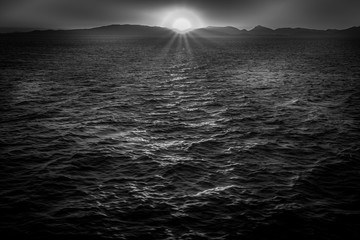Black and white effect of sun about to set behind the Saronic Gulf islands