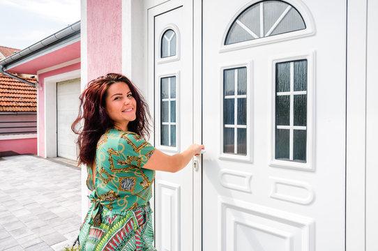Front door. Young woman holds doorknob on front door PVC