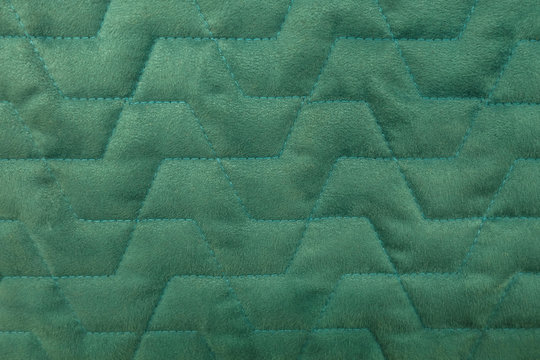 abstract background of green velour quilted fabric close up