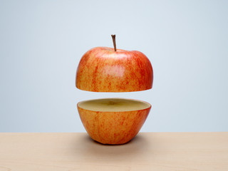 Ripe red apple cut in half with top floating above bottom