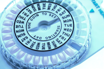 Closeup of birth control pill dispenser showing days of the week