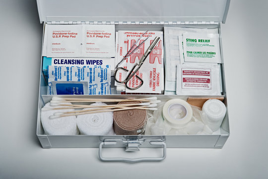 First aid kit packed with medical supplies on grey background