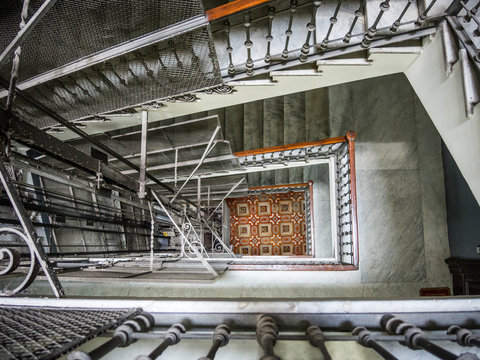 View down European apartment building elevator shaft to lobby tile floor
