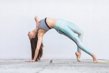 Fotomurales - Fit sporty active girl in fashion sportswear doing yoga fitness exercise in front of gray wall, outdoor sports, urban style.