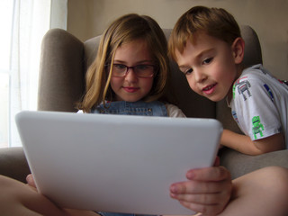 Brother and sister using digital tablet sitting on armchair in living room