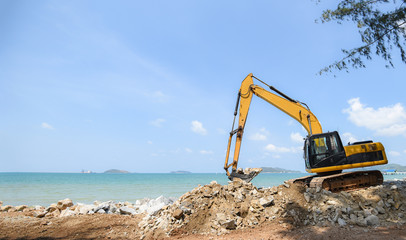 excavator digger stone working on construction site - backhoe loader on the beach sea ocean and blue sky background