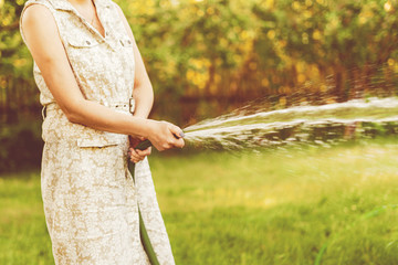 female gardener pouring plants in the garden with water hose